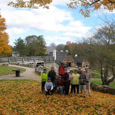 Bicyclists pose for a photo amid colorful fall leaves in Saugus, Mass.