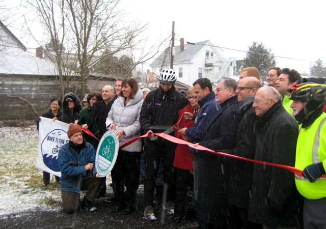Officials pose at a ribbon cutting ceremony near Linden Square in Malden.