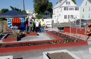 People stand next to raised garden beds in Malden.