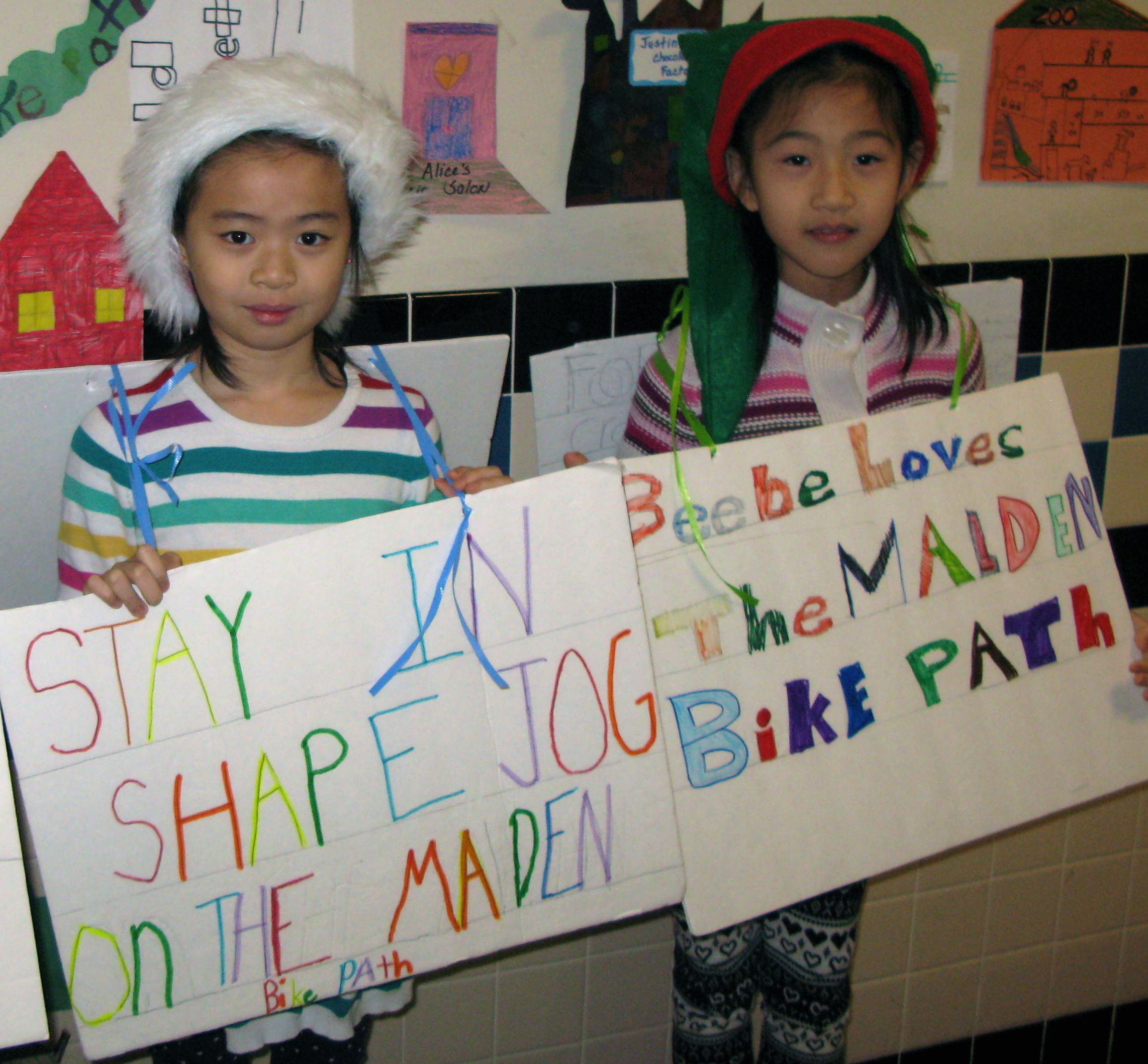 Second grade students hold signs promoting bike path.