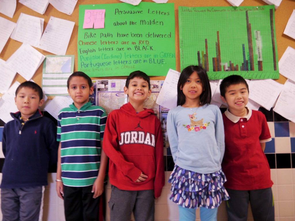 Second-grade students stand before a bulletin board with letters they wrote promoting the bike path.