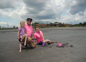 Stephen Winslow poses with two granddaughters on the beach.