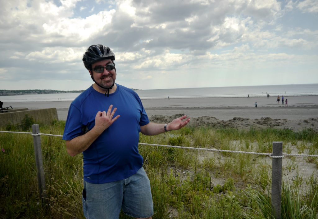 Malden resident holds up three fingers by the beach.