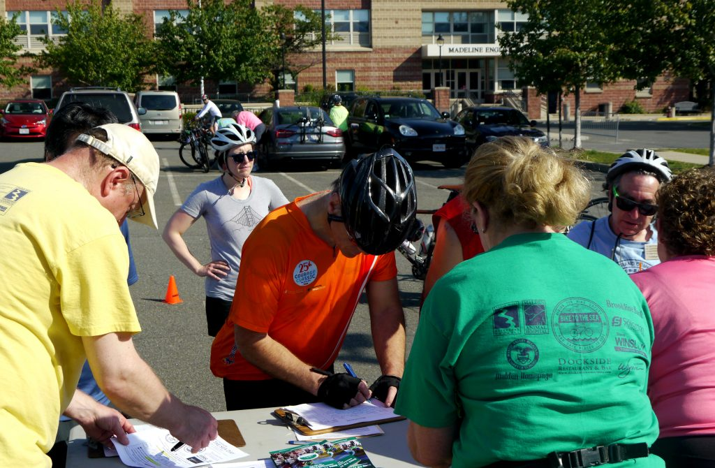 Cyclists sign in at a registration table.