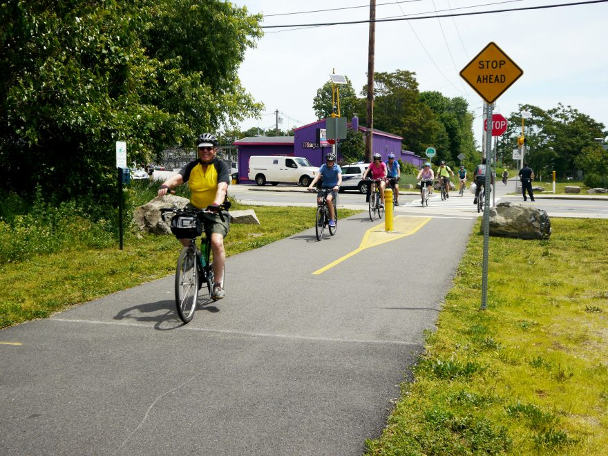Bike riders cross Broadway along the trail in Malden.