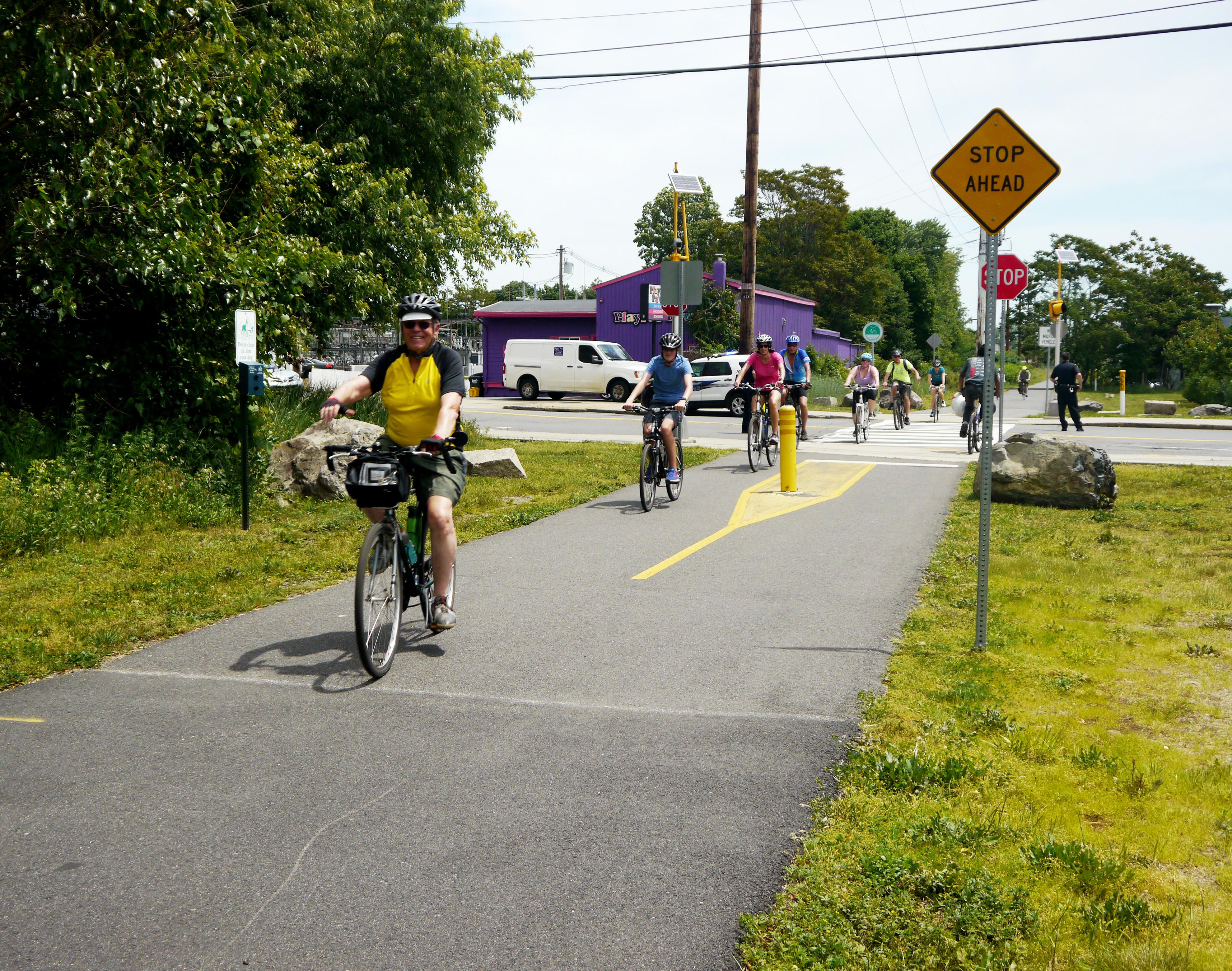 Bike riders cross Broadway along the trail in Malden.