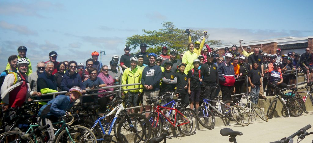 Cyclists pose for a photo at Nahant Beach during the annual