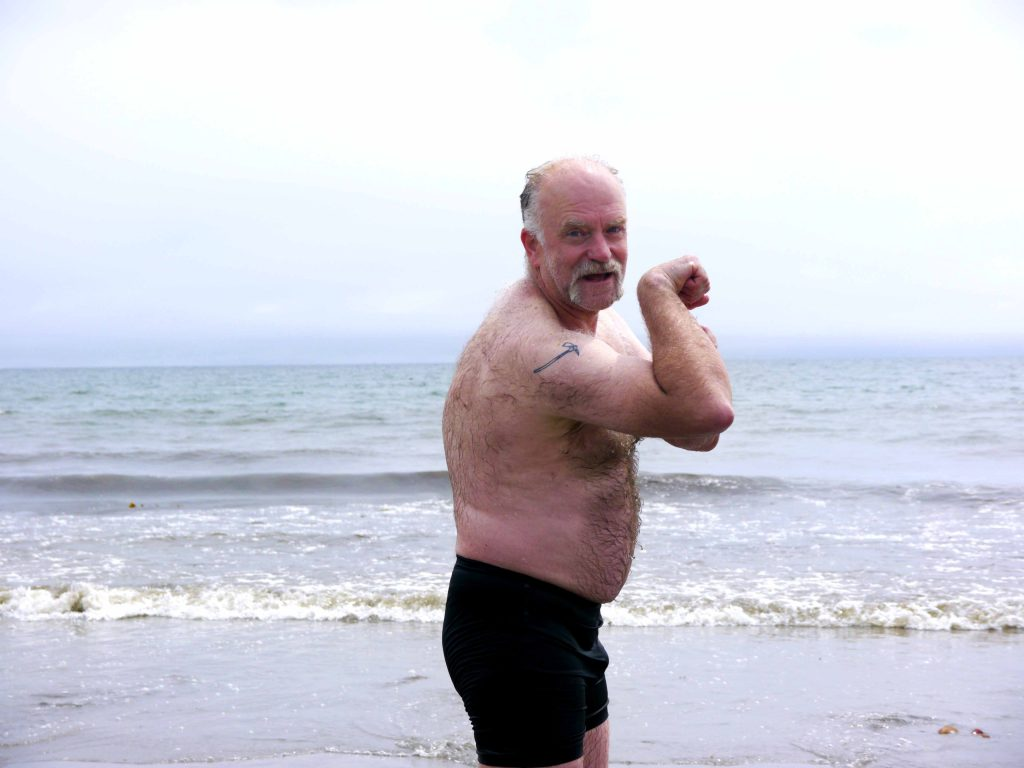 Man shows off his bicep on the beach.