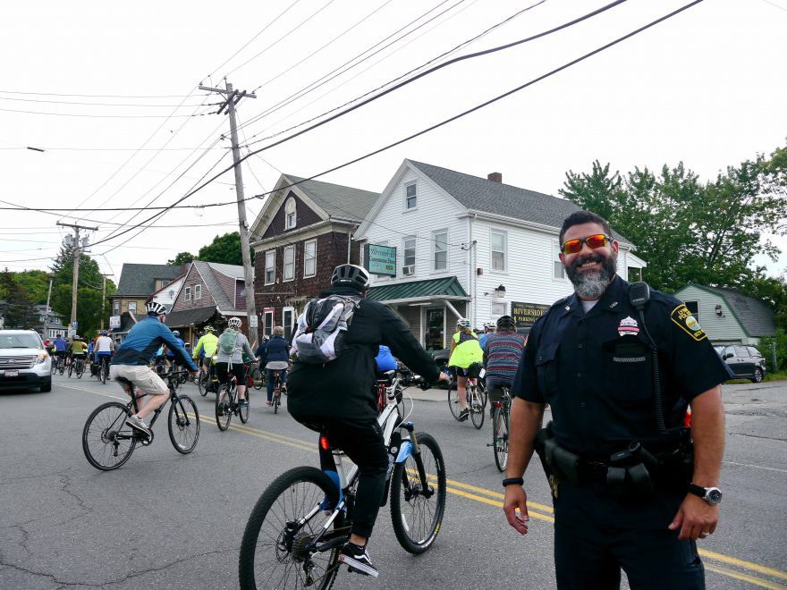 An officer stops traffic for cyclists.