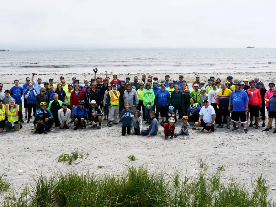 Group photo of cyclists on the beach.
